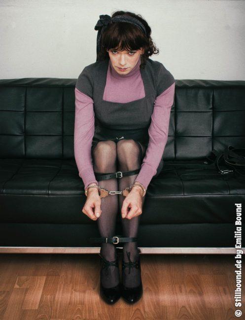 Foto von Emilia Bound auf der Couch in Handschellen